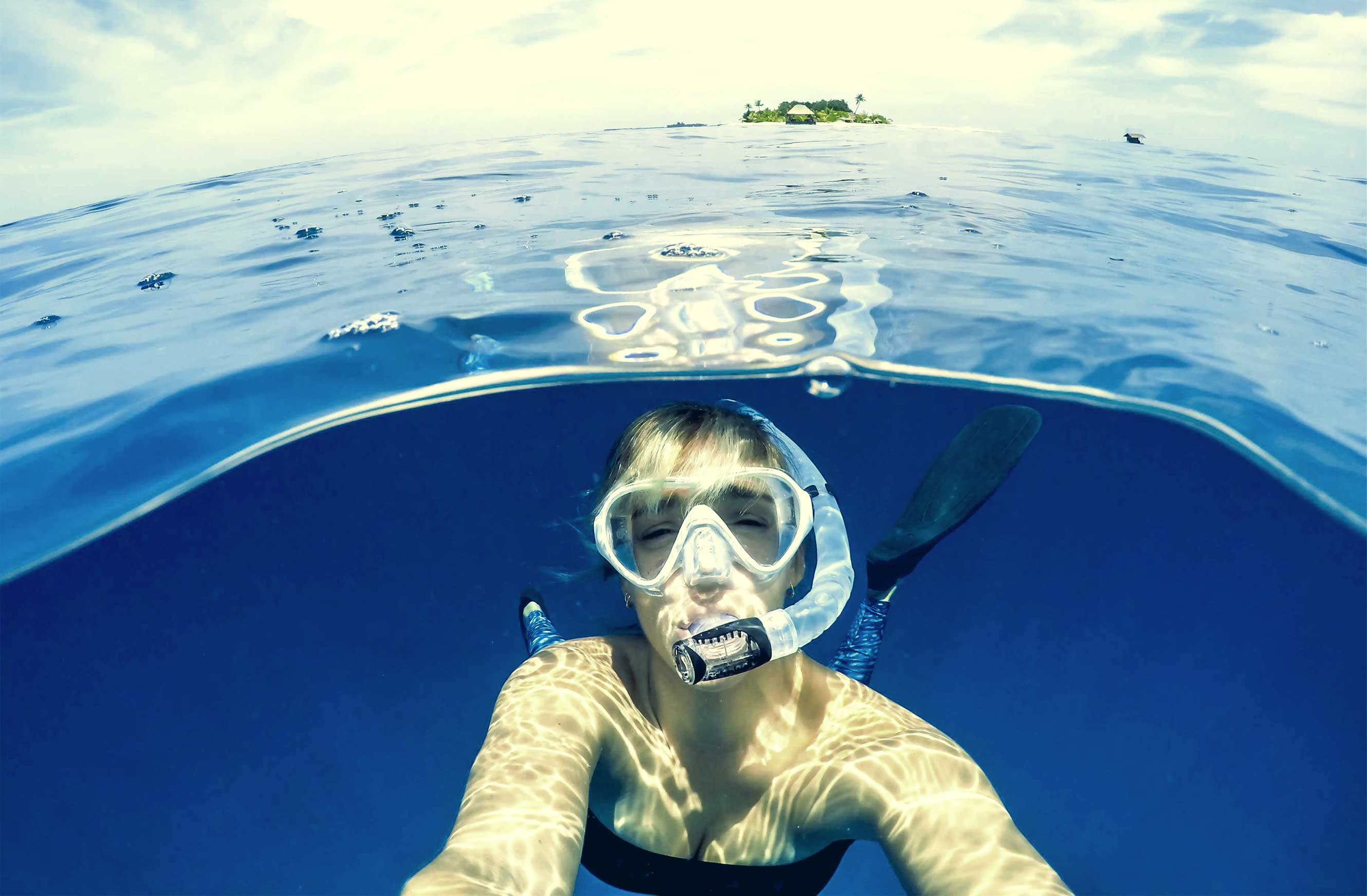 Photo of a woman taking a selfie underwater while wearing a clear mask and snorkel